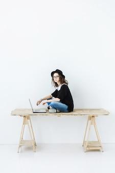 Schöne stilvolle frau, die am laptop sitzt und arbeitet