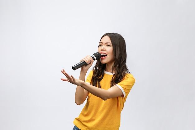 Schöne stilvolle frau, die karaoke singt