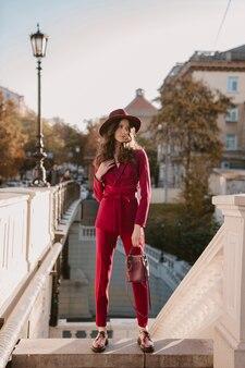 Schöne stilvolle frau im lila anzug, der in der stadtstraße, frühlingssommer-herbstsaison-modetrend trägt hut trägt und geldbörse hält