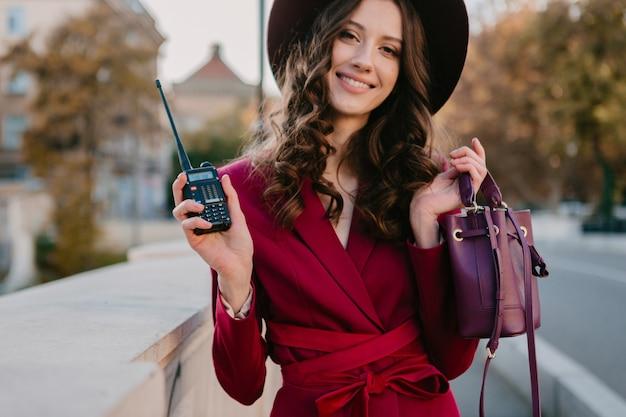 Schöne stilvolle frau im lila anzug, die in stadtstraße, modetrend der frühlingssommerherbstsaison trägt hut trägt und geldbörse hält walkie-talkie hält