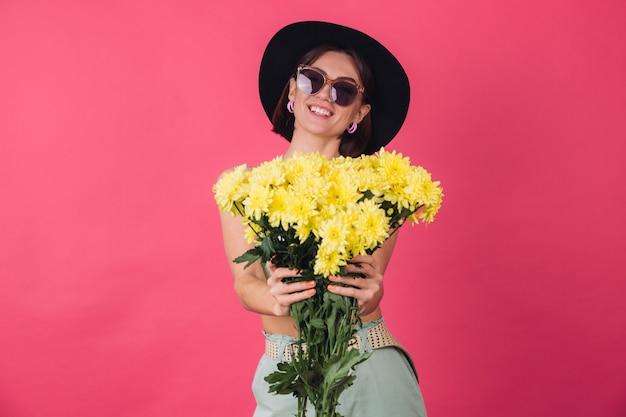 Schöne stilvolle frau in hut und sonnenbrille posiert, hält großen strauß gelber astern, frühlingsstimmung, positive emotionen isoliert