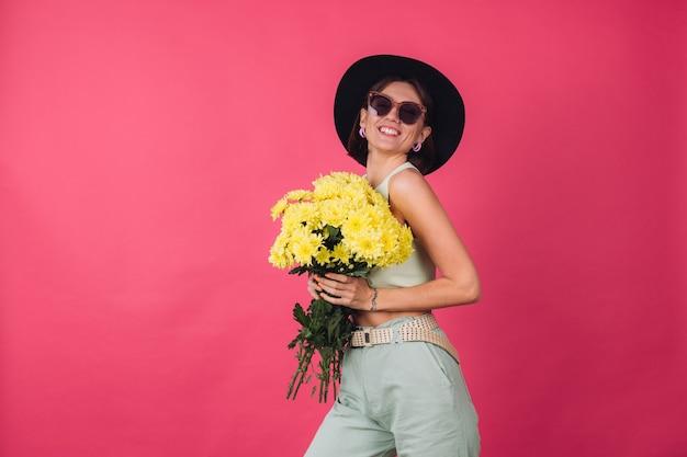Schöne stilvolle frau in hut und sonnenbrille posiert, hält großen strauß gelber astern, frühlingsstimmung, positive emotionen isolierten raum