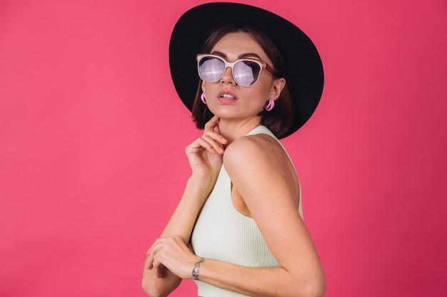 Schöne stilvolle frau in hut und sonnenbrille posiert