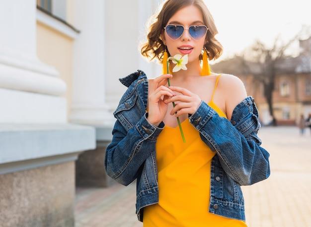 Schöne stilvolle hipster frau posiert, straßenmode, hält blume, gelbes kleid, jeansjacke, boho-stil, frühling sommer modetrend, lächeln, trendige blaue sonnenbrille, lächelnd, sonnig, accessoires