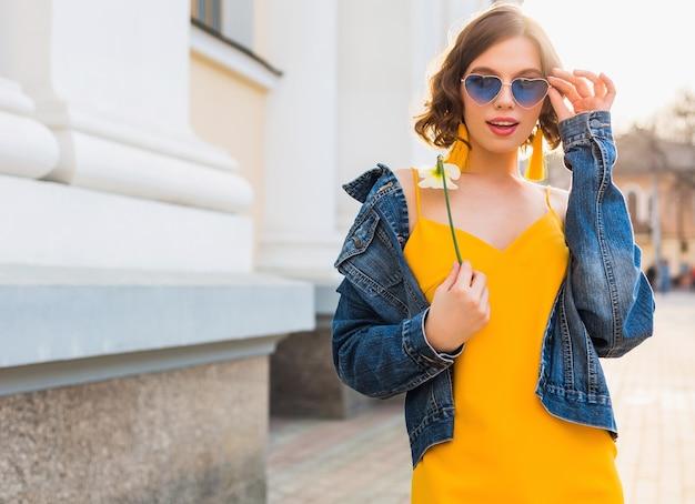 Schöne stilvolle hipster frau posiert, straßenmode, hält blume, gelbes kleid, jeansjacke, boho-stil, frühling sommer modetrend, lächeln, trendige blaue sonnenbrille, lächelnd, sonnig