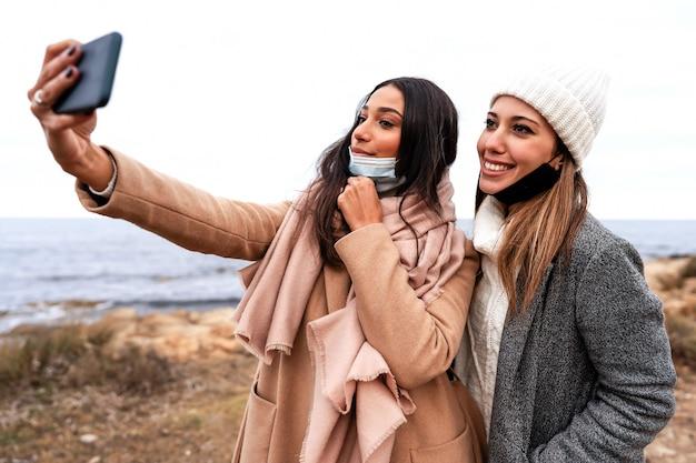 Schöne stilvolle hispanische frau, die selfie im freien im seewinterurlaub mit ihrer kaukasischen freundin macht, die gesenkte schutzmaske trägt