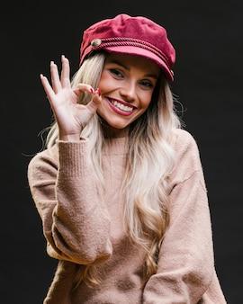 Schöne stilvolle junge frau, welche die rosa kappe zeigt die okaygeste steht gegen schwarzen hintergrund trägt