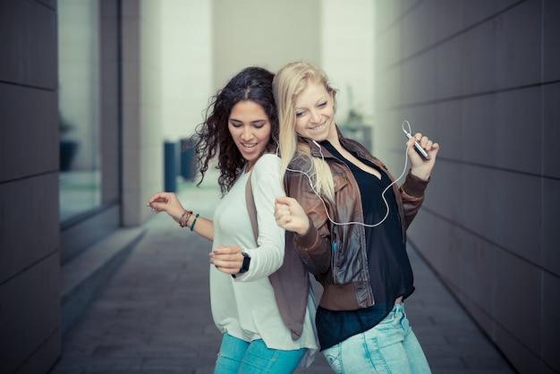 Schöne stilvolle junge frauen der blondine und des brunette