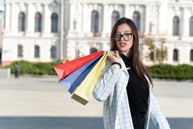 Schöne stilvolle käuferin mit bunten einkaufstaschen auf schönem gebäude
