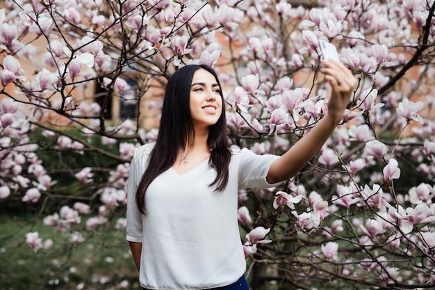 Schöne stilvolle kaukasische frau, die selfie im blütenmagnoliengarten macht. frühlingszeit