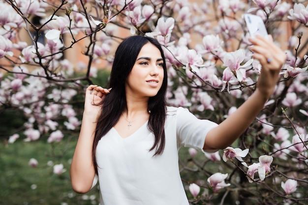 Schöne stilvolle kaukasische frau, die selfie im blütenmagnoliengarten macht. untersicht