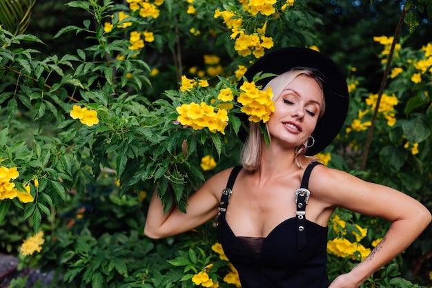Schöne stilvolle kaukasische glückliche frau im schwarzen kleid und im klassischen hut im park, umgeben von gelben thailändischen blumen