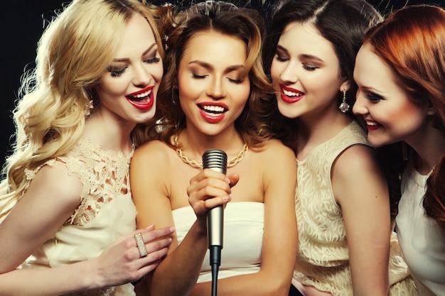 Schöne stilvolle mädchen, die karaoke singen