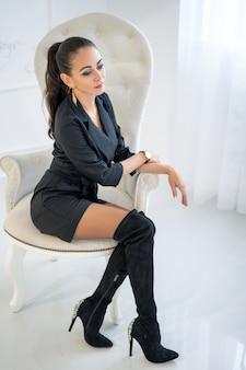 Schöne stilvolle überzeugte frau, die in einem weißen stuhl im studio sitzt