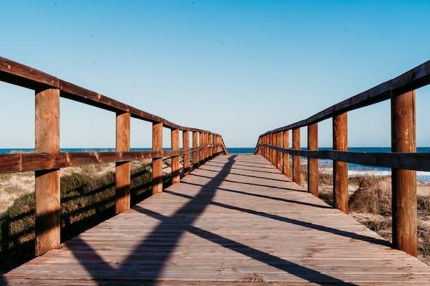 Schöne strandlandschaft bei sonnenuntergang. holzbrückenweg. blauer himmel