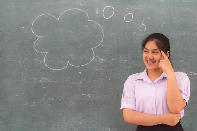 Schöne studentin, die an der blackbord im klassenzimmer denkt und lächelt.