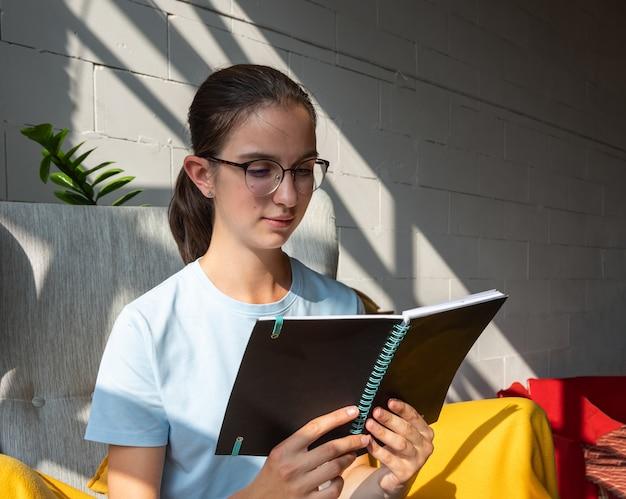 Schöne studentin, die ein buch liest, während sie auf einem sessel in einem café mit stilvollen diagonalen schatten sitzt, hartes licht. konzept des lesens von papierbüchern. zurück zum schulkonzept. freiberufliches konzept