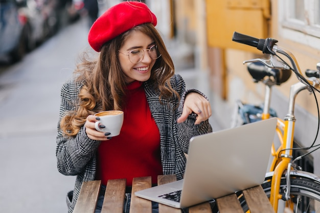 Schöne studentin in der roten baskenmütze, die kaffee trinkt, während sie mit computer arbeitet