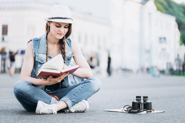 Schöne studentin liest ein buch beim sitzen auf dem asphalt in der mitte der straße