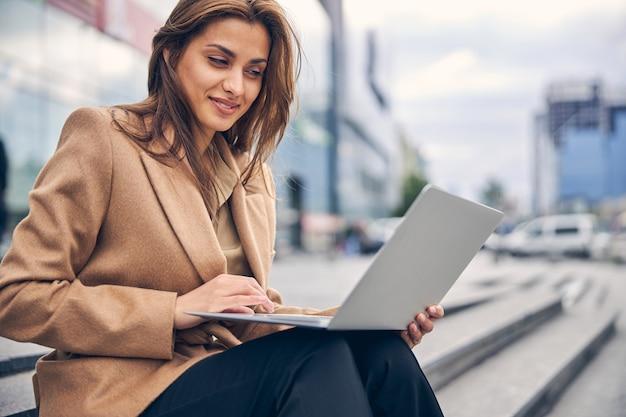 Schöne stylische freiberuflerin mit einem zufriedenen lächeln, die auf der treppe an ihrem computer arbeitet