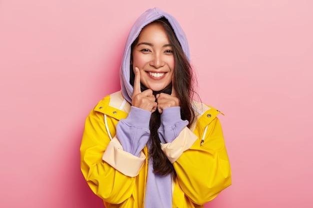 Schöne süße asain mädchen trägt lila kapuzenpulli, gelben wasserdichten regenmantel, hält zeigefinger auf den wangen, drückt positive emotionen aus