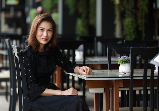 Schöne süße asiatische frau im schwarzen kleid, die allein im lebensmittelladen im freien sitzt und zur kamera schaut.