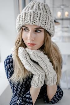 Schöne süße frau, die gestrickte wintermütze und handschuhe auf caféhintergrund trägt.
