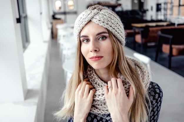 Schöne süße frau, die gestrickte wintermütze und schal auf caféhintergrund trägt.