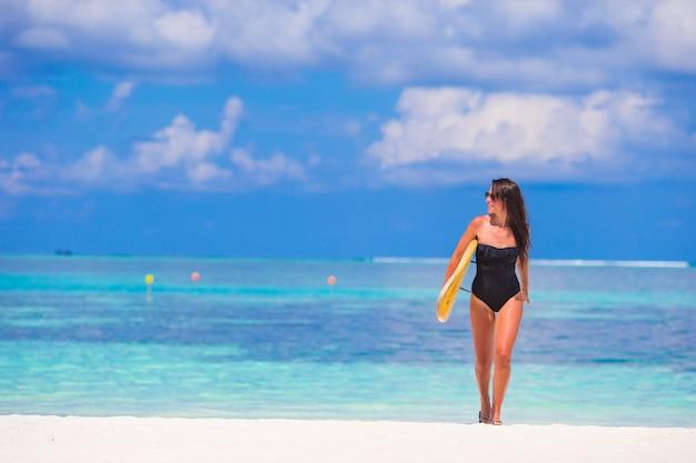 Schöne surferfrau, die während der sommerferien surft