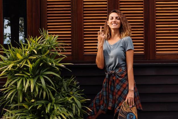 Schöne tätowierte passformfrau in jeansshorts, kariertes hemd mit longboard