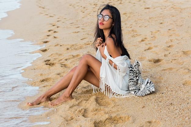 Schöne tan asiatische frau mit roten lippen sitzen auf senden in der nähe von meer in weißen strand böhmischen outfit stilvolle frau ruhen auf tropischen strand urlaub und urlaubskonzept