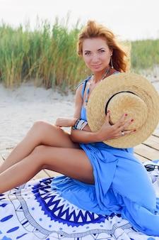 Schöne tan schlanke rothaarige frau mit stilvollen accessoires, die auf sonniger küste nahe ozean aufwerfen. zughut, blaues boho-kleid.