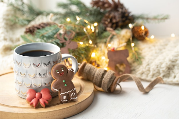 Schöne tasse mit lebkuchenplätzchen verziert mit glasur nah oben auf einem unscharfen hintergrund mit dekor.