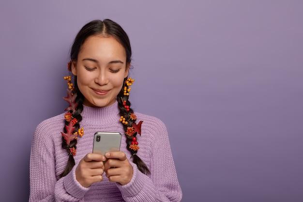 Schöne tausendjährige brünette frau hat zwei zöpfe mit festsitzenden herbstblättern als naturkosmetik, konzentriert in smartphone