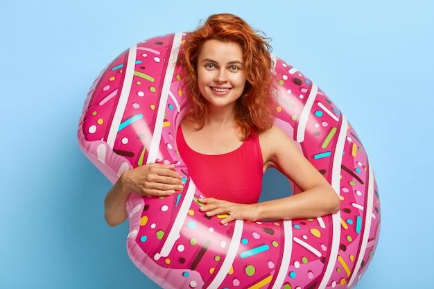 Schöne tausendjährige frau mit gewelltem rotem haar, das gegen die blaue wand mit schwebendem donut aufwirft