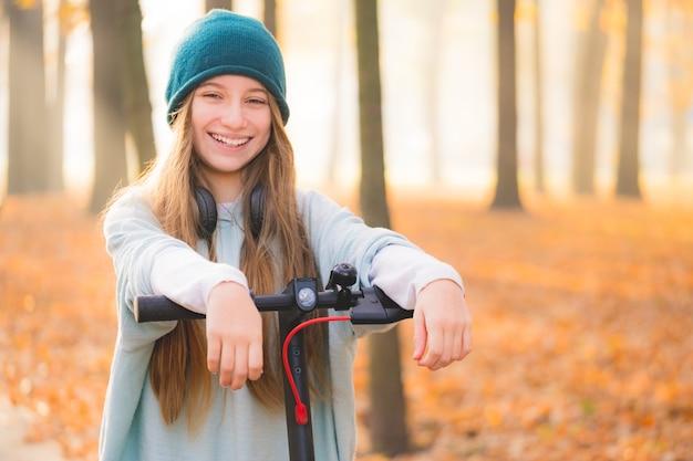 Schöne teenager-mädchen mit roller ruht im herbstpark