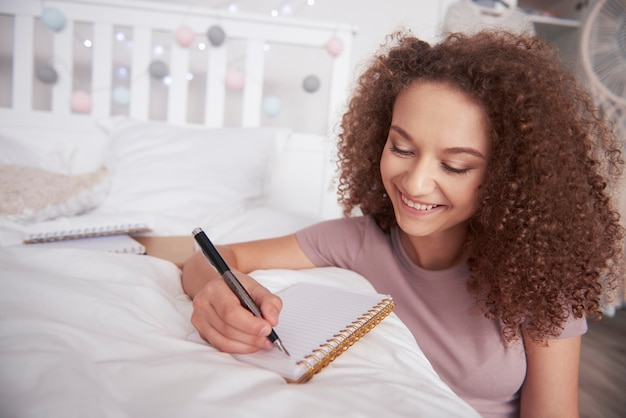 Schöne teenager-mädchen schreiben tagebuch