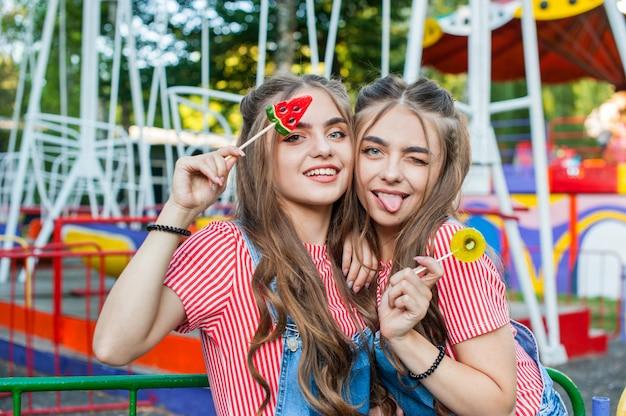 Schöne teenager-zwillingsschwestern in bunten kleidern mit lutscher-karamell auf bunten messegeländen attraktionen