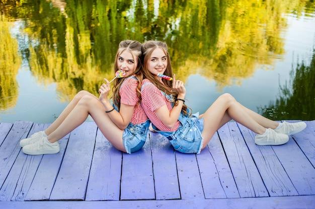 Schöne teenager-zwillingsschwestern in bunten kleidern mit lutschern, die auf farbigen brettern sitzen