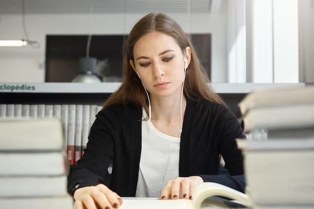 Schöne teenagerfrau mit langen brünetten haaren, die uniform tragen, die lehrbuch oder handbuch studiert und ihre lieblingsmusik mit kopfhörern beim sitzen in der schulbibliothek hört