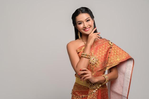 Schöne thailändische frau, die ein thailändisches kleid und ein glückliches lächeln trägt.