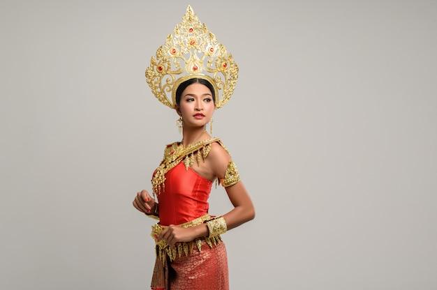 Schöne thailändische frau, die thailändisches kleid trägt und die spitze betrachtet