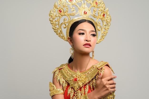 Schöne thailändische frau, die thailändisches kleid trägt und umarmend steht