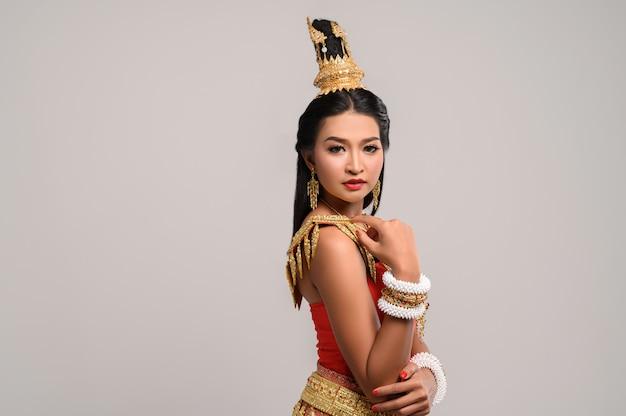 Schöne thailändische frau, die thailändisches kleid trägt und zur seite schaut