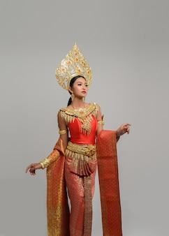 Schöne thailändische frau, die thailändisches kleid und die aufstellung trägt