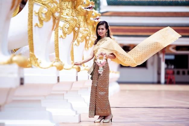 Schöne thailändische frau im thailändischen traditionellen kostüm am tempel