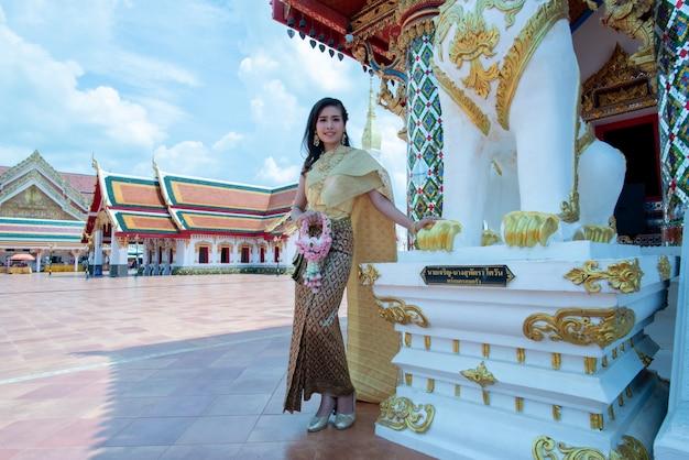 Schöne thailändische frau im trachtenkostüm am tempel von thailand