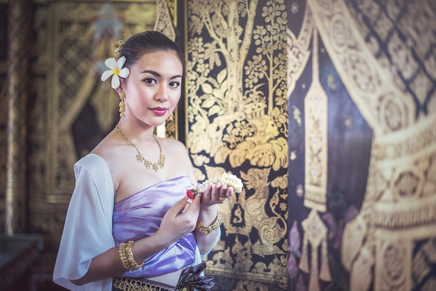 Schöne thailändische frau im traditionellen thailändischen kleid