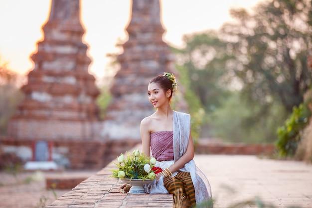 Schöne thailändische mädchen im thailändischen traditionellen kostüm, das versucht, lotosblume zur sonnenuntergangzeit oben zu rollen