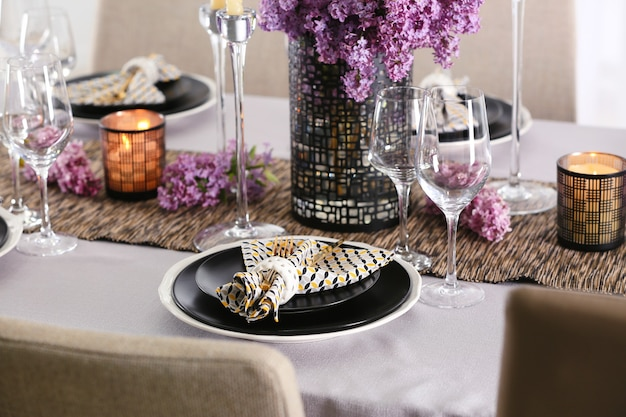 Schöne tischdekoration mit goldenem besteck und flieder